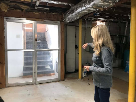 Kathy McGuire shows the entrance to her home's basement, which was once used for dog fighting.