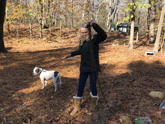 Kathy McGuire holds up heavy metal chains left behind by her home's former owners, who ran a dog fighting ring on the property. The backyard is filled with mounds where McGuire believes dogs are buried.