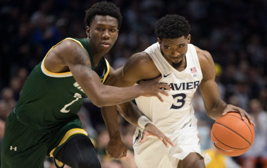 Xavier Musketeers guard Quentin Goodin (3) drives on Siena Saints guard Gary Harris Jr. (2) in the second half of the NCAA basketball game on Friday, Nov. 8, 2019, at Xavier University's Cintas Center in Evanston.