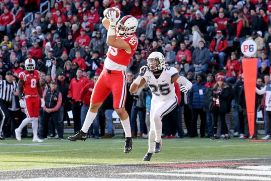 Cincinnati Bearcats tight end Josiah Deguara (83) catches a touchdown as Connecticut Huskies defensive back Tyler Coyle (25) defends in the first quarter of a college football game, Saturday, Nov. 9, 2019, at Nippert Stadium in Cincinnati.