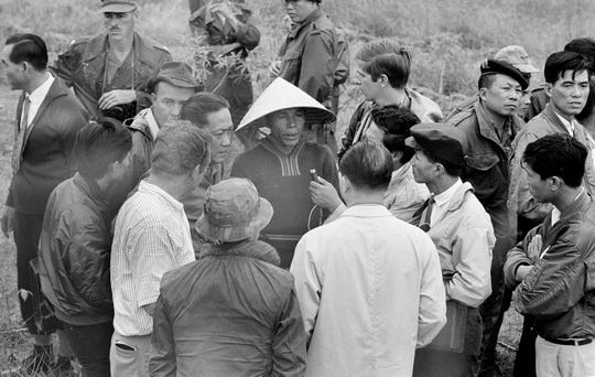 A man points out to Sen. Tran Van Don, left, the place where he said he found 30 bodies after U.S. troops left My Lai in South Vietnam in March 1968, on Dec. 3, 1969. The man said he was hiding outside the hamlet at the time and declared he did not see Americans kill civilians but heard women crying and gunfire after they entered the hamlet. Man at right is unidentified.