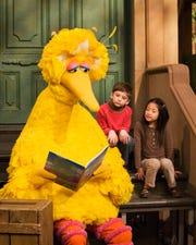 Big Bird reads to Connor Scott and Tiffany Jiao during a taping of Sesame Street on Thursday, April 10, 2008 in New York.