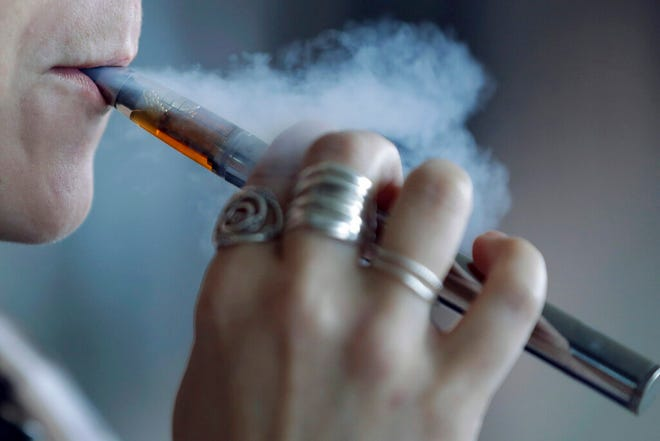 FILE - In this Friday, Oct. 4, 2019 file photo, a woman using a vaping device exhales a puff of smoke in Mayfield Heights, Ohio. The Centers for Disease Control and Prevention confirmed Thursday, Nov. 7, 2019, that new government figures show more than 2,000 Americans have come down with vaping-related illnesses. Illnesses have occurred in every state but Alaska. (AP Photo/Tony Dejak, File)