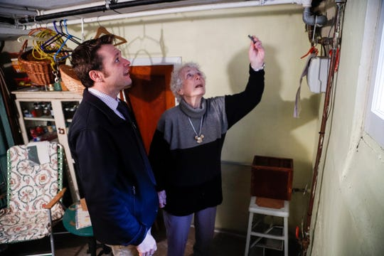 Aaron Filipski, director of Public Services of Royal Oak, talks to Ruth Cleaveland about to check for a lead water-service pipe with a quarter and a magnet at her home in Royal Oak on Nov. 6, 2019.