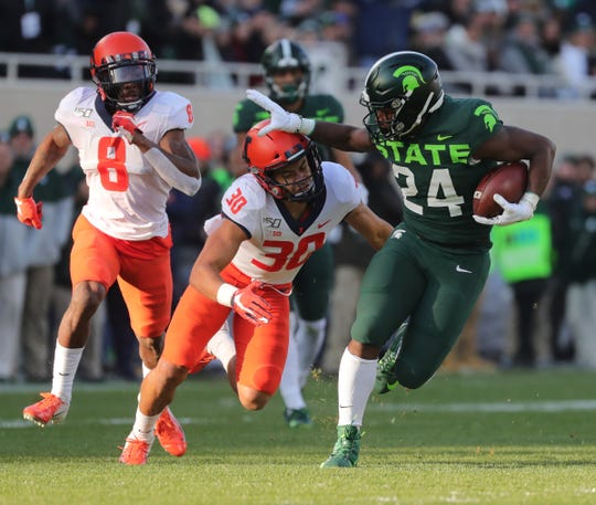 Michigan State Spartans running back Elijah Collins runs by Illinois defensive back Sydney Brown (30) during the first half Saturday, Nov. 9, 2019 at Spartan Stadium.
