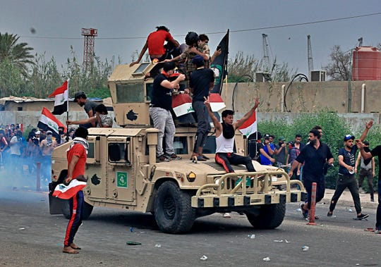 Protesters ride an Iraqi Army armored vehicle during a demonstration in Basra, Iraq, Friday, Oct. 25, 2019.