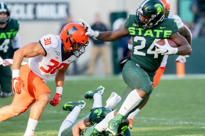 Michigan State running back Elijah Collins pushes away Illinois defensive back Sydney Brown during a run in the first quarter.