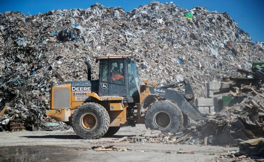 A worker at HONC Recycling moves some of the demolition debris so it can be recycled on Friday, Nov. 1, 2019.