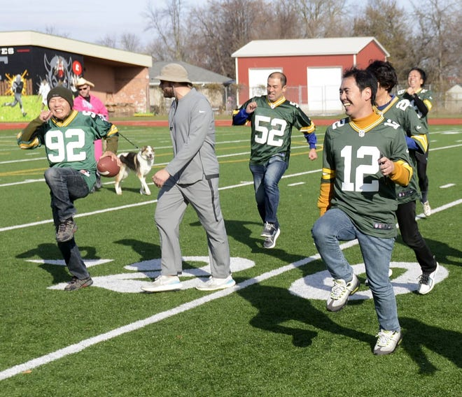 Brian Gajeski of Bode Central in Howard, center, conducts warm-up drills with Japanese Packers Cheering Team members on Nov. 9 at Green Bay East High School.