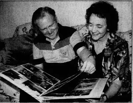 Warren Mack and his wife Margaret look at a photo album.