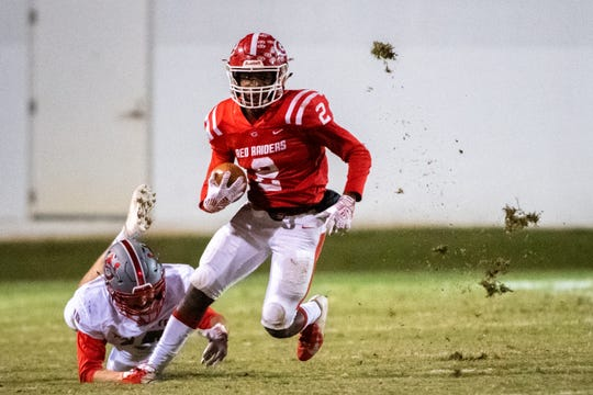 Greenville's Khalique Holland II (2) breaks a tackle attempted by Palmetto senior Zach Cannon (10) in the first round of the Class AAAA playoffs at Sirrine Stadium Friday. Greenville won 49-24.