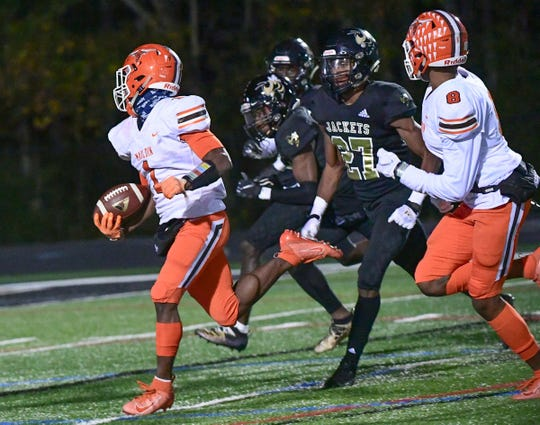 Mauldin's George Ford (1) runs by TL Hanna sophomore Nick Carson(27) during the third quarter at T.L. Hanna High School in Anderson Friday, November 8, 2019.