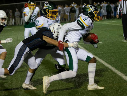 Christ School's Aydan White (9) tries to break a tackle during Friday's NCISAA state championship game at Charlotte Christian