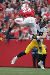 Wisconsin's Jonathan Taylor tries to leap over Iowa's Jack Koerner during the first half of an NCAA college football game Saturday, Nov. 9, 2019, in Madison, Wis. (AP Photo/Morry Gash)