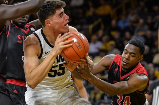 Hawkeyes center Luka Garza (55) and SIU Edwardsville Cougars guard Cam Williams (24) battle for the ball during the first half at Carver-Hawkeye Arena.
