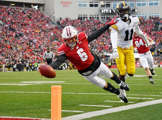 Danny Davis lunches for the first of three Badgers touchdowns, finishing a 17-yard jet sweep past Iowa's Michael Ojemudia.