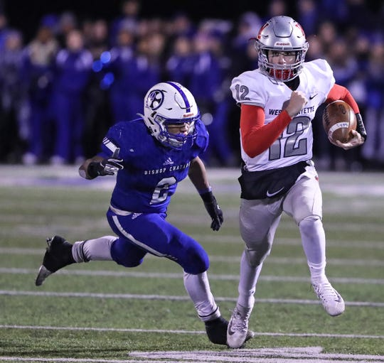 West Lafayette's Kyle Adams (12) runs the ball against Bishop Chatard's Daylen Taylor (2) in the second half of the Class 3A sectional final game at Bishop Chatard High School in Indianapolis, Ind., Friday, Nov. 8, 2019. against the Bishop Chatard defeated West Lafayette 42-14.