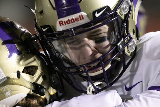 Wes Latson of Fowlerville is comforted as the clock runs out on the Gladiators in the district final game against Flint Powers Catholic Friday, Nov. 8, 2019.