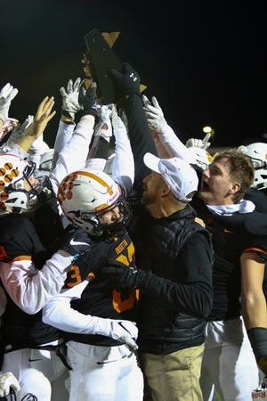 Brighton celebrates with its first district championship trophy since 2005 following a 48-26 victory over East Kentwood on Friday, Nov. 8, 2019.