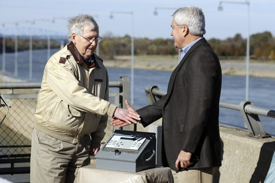 Sen. Mitch McConnell, R-Ky., left, and Rep. James Comer, R-Ky., shake hands after pressing the power button for a bio-acoustic fish fence at the Barkley Lock and Dam where the Cumberland River meets Lake Barkley Friday, Nov. 8, 2019, in Grand Rivers, Ky. The noise-making, bubbling barrier has been installed in the lock to deter the spread of destructive Asian carp .