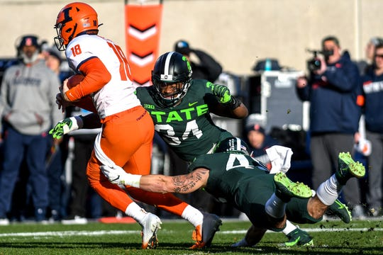 Michigan State's Antjuan Simmons, center, and Noah Harvey, right, tackles Illinois' quarterback Brandon Peters during the first quarter on Saturday, Nov. 9, 2019, at Spartan Stadium in East Lansing.