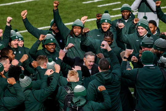 Michigan State head coach Mark Dantonio, center, and the Spartans cheer in the end zone before the game against Illinois on Saturday.