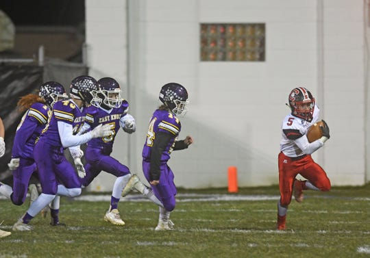 Crestview's Brent Eicher is pursued by a gang of East Knox defenders Friday night at Chet Looney Stadium in Howard, Ohio.