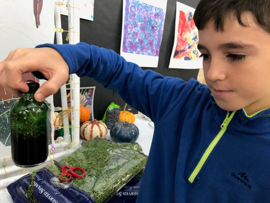 Alvaro Espinosa, 10, added Gillyweed, also known as moss, to his glass jar of potion Saturday at the Mansfield Art Center.
