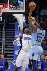 The Memphis Grizzlies' Jaren Jackson Jr. (13) shoots over the Orlando Magic's Jonathan Isaac (1) during the first half on Friday in Orlando.