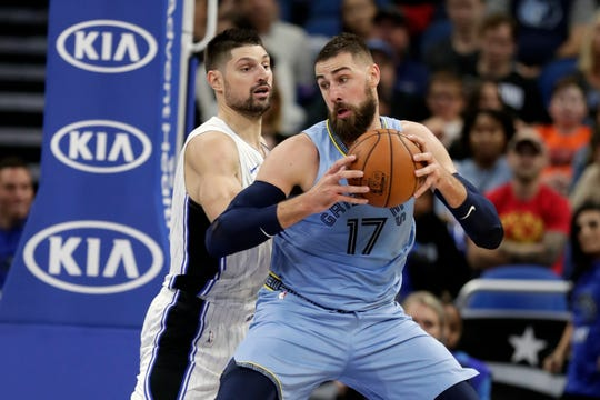 The Memphis Grizzlies' Jonas Valanciunas (17) makes a move to the basket against the Orlando Magic's Nikola Vucevic, left, during the first half on Friday, Nov. 8, 2019, in Orlando, Fla.