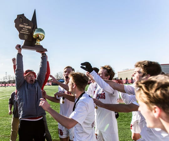 Sturgeon Bay coach Todd Maas hoists the Division 4 state championship trophy after his team defeated The Prairie School 2-1 on Saturday at Uihlein Soccer Park in Milwaukee.