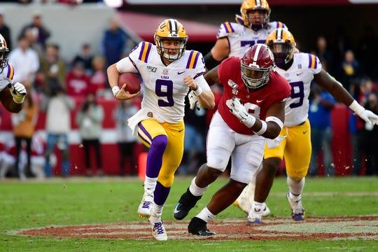 LSU quarterback Joe Burrow (9) runs as Alabama defensive lineman Phidarian Mathis (48) chases him in the first half of an NCAA college football game, Saturday, Nov. 9, 2019, in Tuscaloosa , Ala. (AP Photo/Vasha Hunt)
