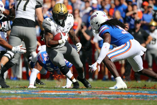 Vanderbilt Commodores running back Ke'Shawn Vaughn (5) runs with the ball as Florida Gators linebacker David Reese II (33) and defensive back Shawn Davis (31) tackle during the first quarter at Ben Hill Griffin Stadium.