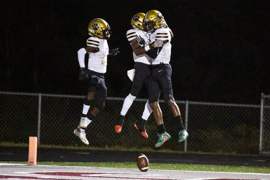 From left to right, Moore Haven High School Football team's Ja'evion Carey, Johnny Crawford iii, and Javon Jones celebrate their first touchdown during a Class 2A-Region 4 football playoff game on Friday, November 8, 2019, at First Baptist Academy.