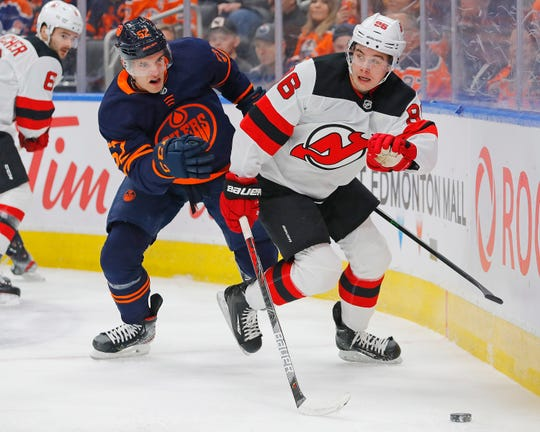 Edmonton Oilers forward Patrick Russell (52) and New Jersey Devils forward Jack Hughes (86) chase a loose puck during the first period at Rogers Place.