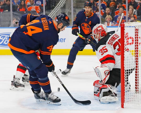 Edmonton Oilers forward Zack Kassian (44) tries to tip a pass by New Jersey Devils goaltender Cory Schneider (35) during the first period at Rogers Place.