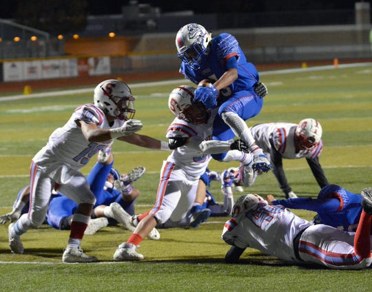 Las Cruces running back Johnny Terrazas jumps over the Sandia defense to score in the first quarter during their playoff game at Field of Dreams on Friday.