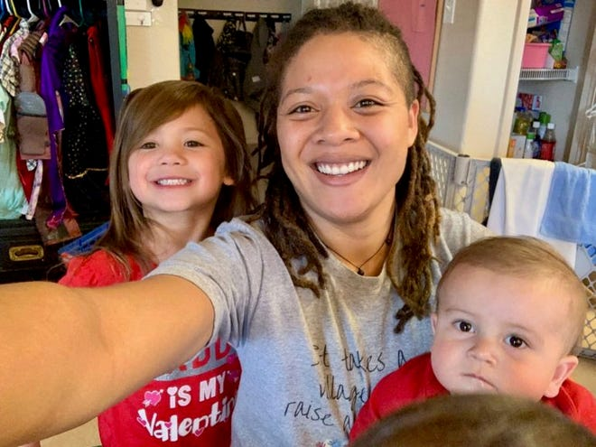 Michelle Masiwemai takes a selfie with some of the children she cared for at Best of the Southwest day care center in Las Cruces.