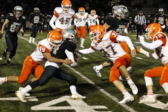 Artesia's defense, led by Dominic Pacheco (49) and Aaron Harmon (37) stop a Capital runner during Friday's 5A state playoff game on Nov. 8, 2019. Artesia won, 56-35 and advances to the quarterfinals next week.