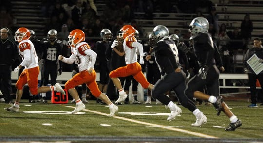 Artesia's Erik Cueto (11) get blocks from teammates Braxton McDonald (10) and Marc Anthony Almanza (30) on his way to a 65-yard kickoff return for a touchdown in the second half against Capital on Nov. 8, 2019. Artesia won, 56-35 and Cueto scored three touchdowns for the Bulldogs.