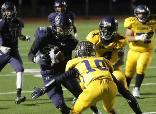 Piedra Vista's Jarrod Mitchell fights for extra yards against Highland's Nathan Lopez (10) and Paul Elumba (4) during Friday's 5A state football playoff opener at Hutchison Stadium in Farmington.