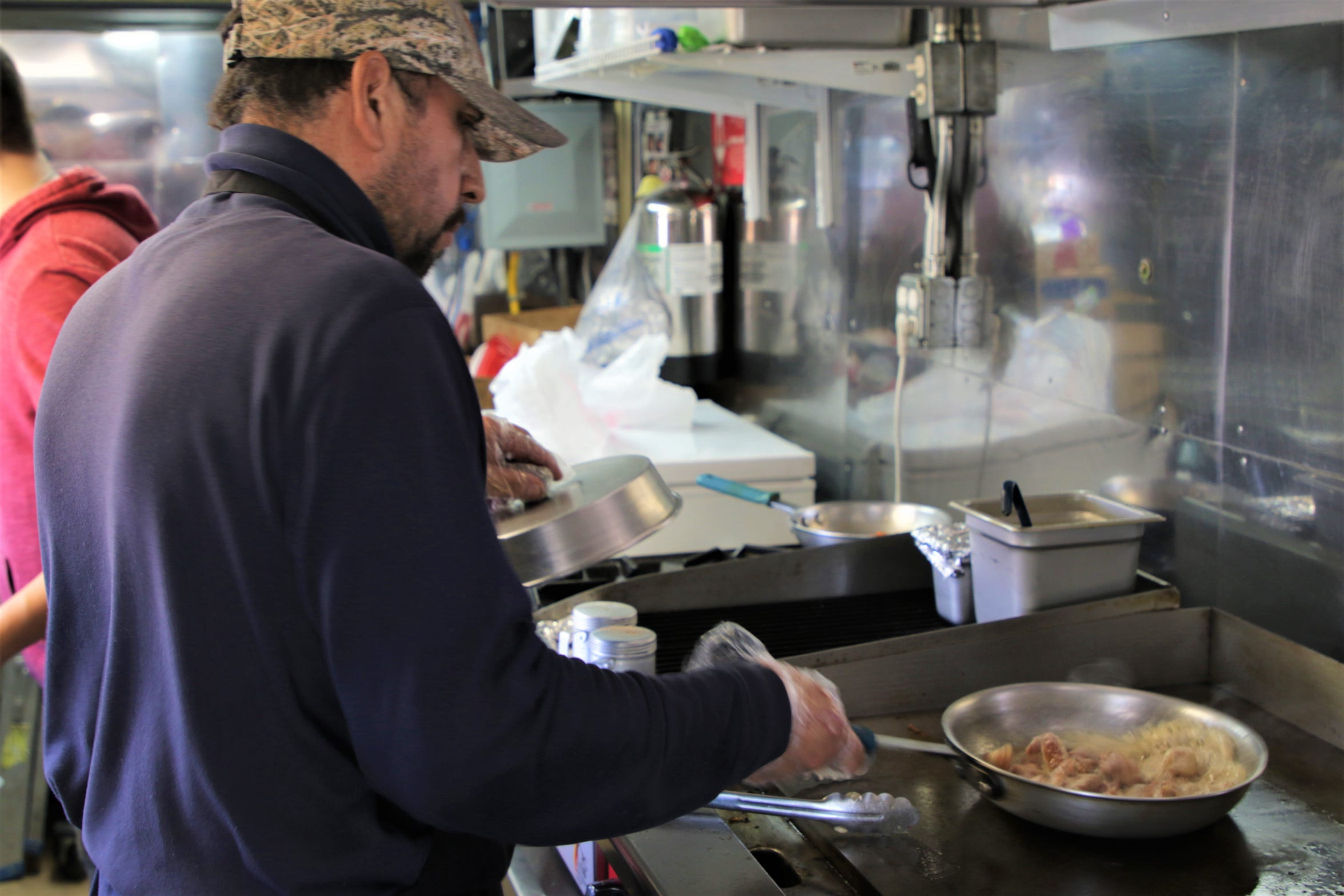 Owner of El Torito food truck Rafael Mercado cooks inside his food truck in Farmington on Nov. 7, 2019.