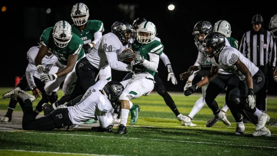 Plymouth's Spencer Korroch (9) and Andrew Uhlian bring down a West Bloomfield ball carrier.