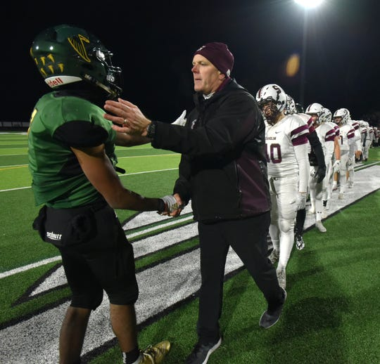 Seaholm football coach Jim Dewald congratulates Groves players at the end of the game.