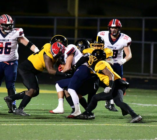 Livonia Franklin's James Carpenter is tackled by a swarm of Crusaders.