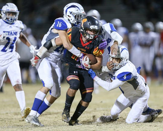 Three Temescal Canyon defenders wrap up Palm Desert running back Simon Gaete on Friday night in the CIF playoffs. Gaete ran for 219 yards and a touchdown in the Aztecs' win.