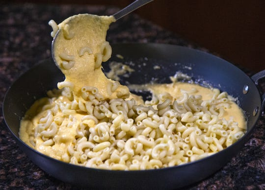Chef and author Robin Miller stirs the pasta into the creamy cheese sauce.