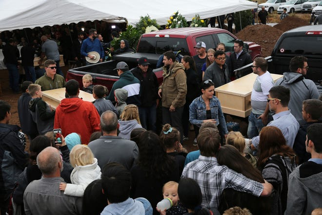Family and friends unload the coffins that contain the remains of Rhonita Miller and four of her young children Krystal and Howard, and twins Titus and Tiana, who were murdered earlier in the week, for a burial service at the cemetery in Colonia Le Baron, Mexico, Friday, Nov. 8, 2019.