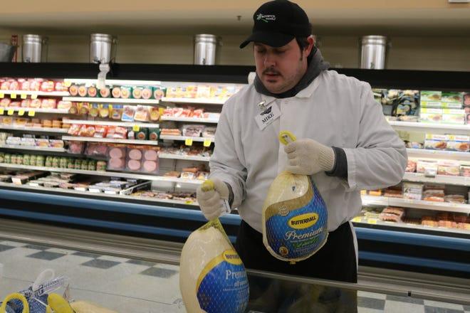 Michael Hopkins, of Bassett's Market, stocks Butterball turkeys on Saturday.