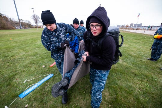 U.S. Naval Sea Cadet Corps students Nickolas Regan, left, and Jacob Vanbuskirk work with a group to carry a student back to the starting line of a team-building PT exercise Saturday, Nov. 9, 2019, in Port Huron. The activity required students to move single-file along wooden plans while carrying objects through obstacles. If one group member fell off the plank, the rest had to carry them back to the start and begin again.